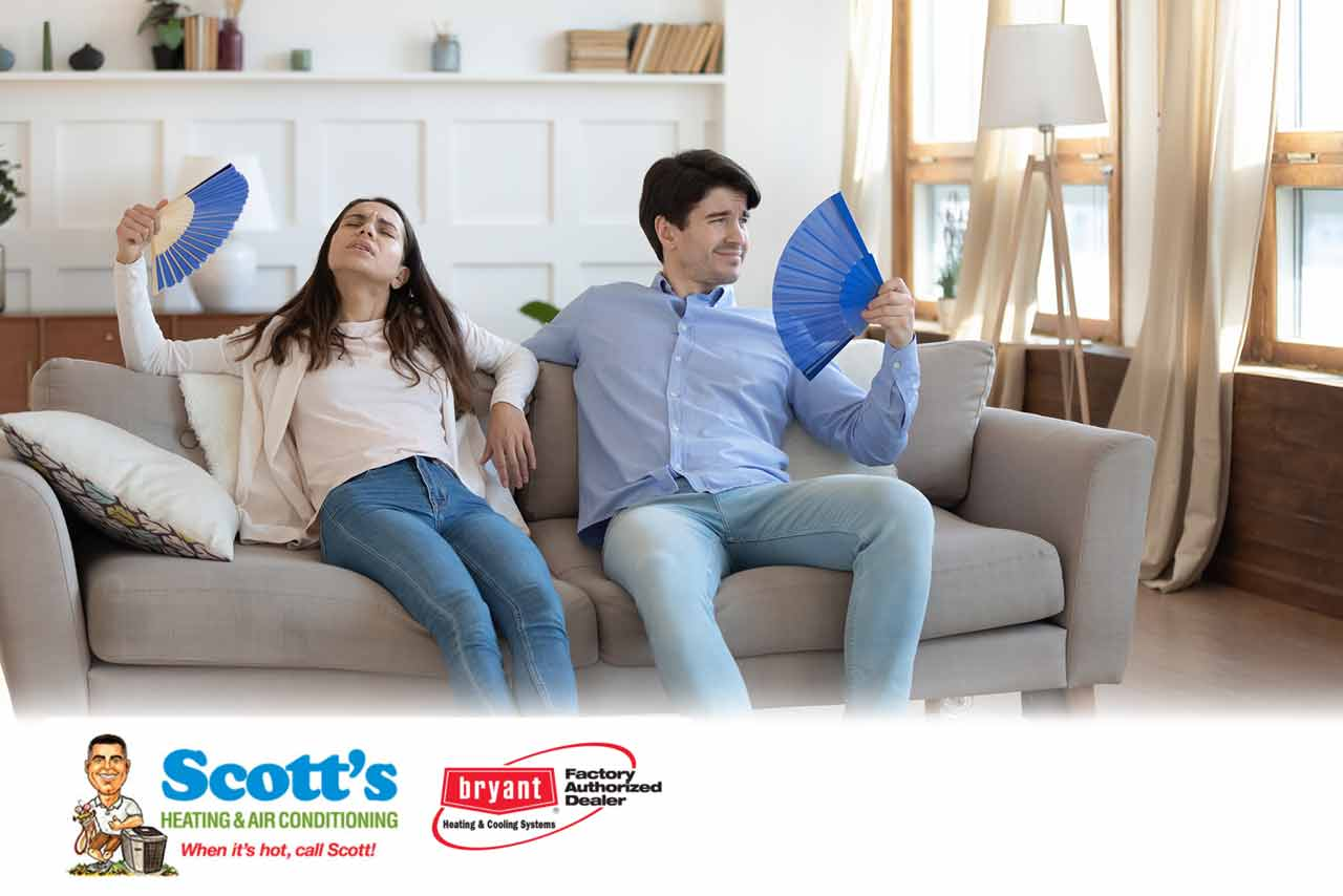 Overheated couple sitting in their home that has imbalanced indoor humidity levels.